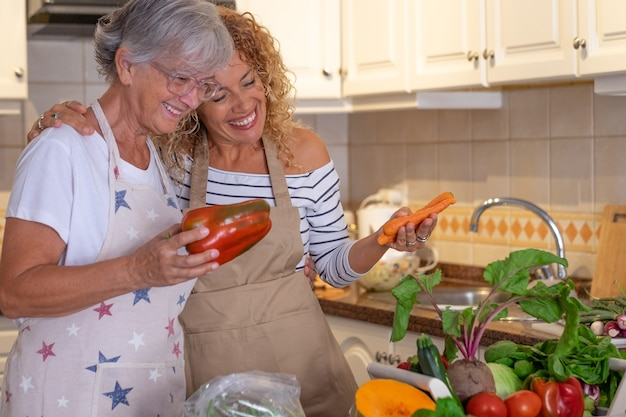 Bella donna riccia matura nella cucina di casa con sua madre che prepara insieme le verdure. crudo fresco raccolto in tavola