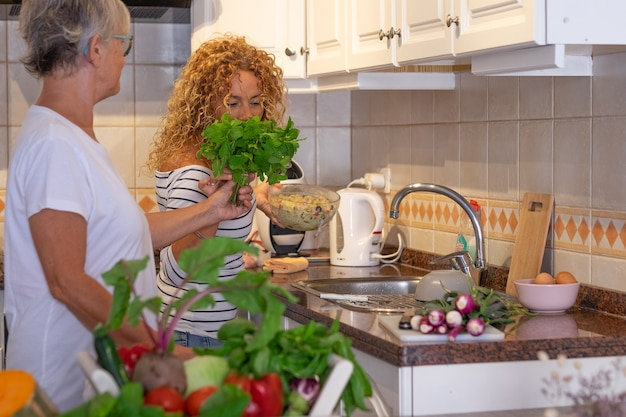 Bella donna riccia matura nella cucina di casa con sua madre che prepara le verdure insieme annusando un mazzo di menta. crudo fresco raccolto in tavola