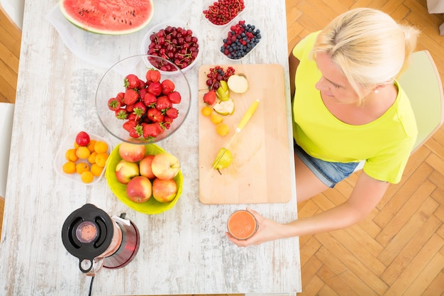 Una bella donna matura che gode di un frullato o di un succo di frutta in cucina.