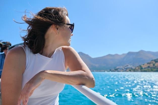 La bella donna matura gode del viaggio di mare di estate