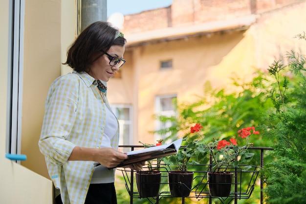 Bella donna matura in abiti domestici sul balcone aperto che legge la rivista, copia dello spazio. balcone di casa decorato con piante e fiori verdi
