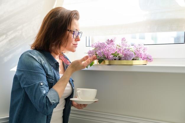 Bella donna matura a casa con fiori, donna sorridente in piedi vicino alla finestra con una tazza di tè e bouquet di lillà, copia dello spazio