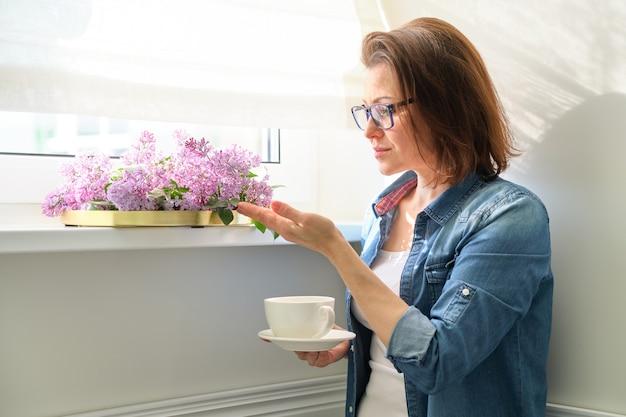 Bella donna matura a casa con i fiori