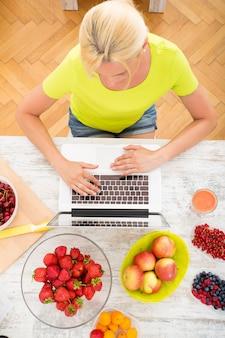 Una bella donna matura utilizzando un computer portatile in cucina con la frutta.
