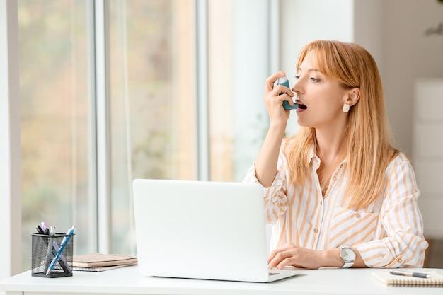 Bella donna matura con inalatore per l'asma in ufficio
