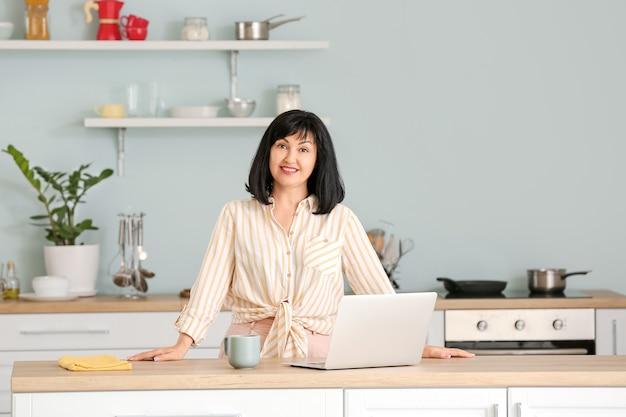 Bella donna matura con laptop in cucina