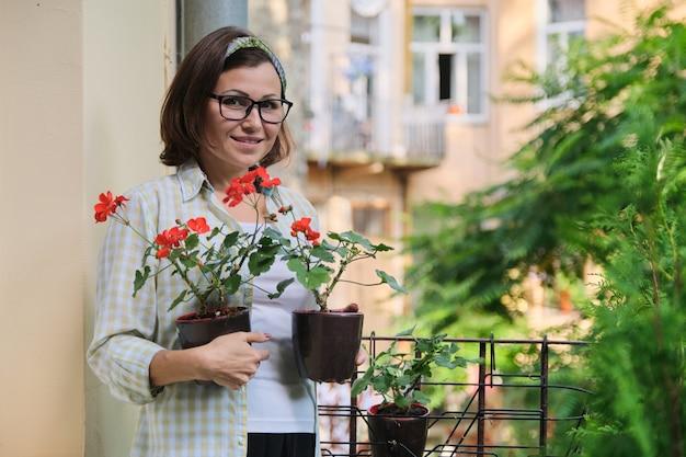 Bella donna matura con fiori estivi in vaso rosso sorridente al balcone di casa all'aperto