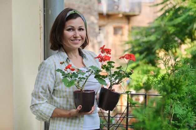 Bella donna matura con i fiori rossi conservati in vaso di estate che sorridono al balcone domestico all'aperto