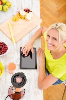 Una bella donna matura con un frullato in cucina utilizzando un tablet.