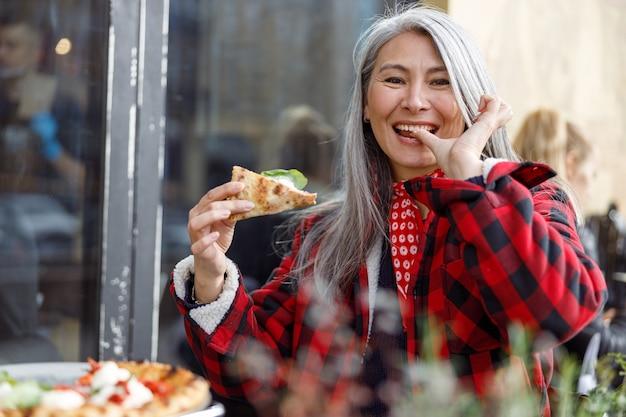 La bella donna asiatica matura sta mangiando la pizza nella terrazza del caffè