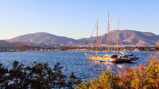 Bellissima costa mediterranea con montagne di isole e yacht al tramonto
