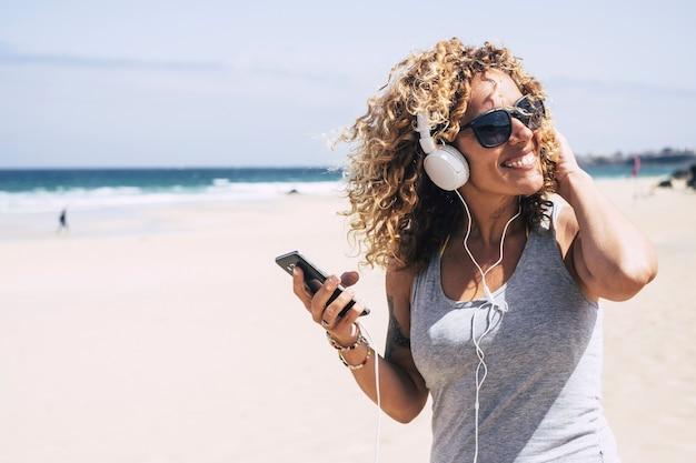 Bella signora caucasica di mezza età gode della libertà e del divertimento di una vacanza in spiaggia nell'isola tropicale e in un bel resort. sorridi e guarda il sole ascoltando musica con lo smartphone internet