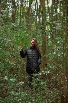 Bella donna bionda di mezza età da sola a piedi attraverso il bosco tra le foglie degli alberi nel bosco. 40 anni.