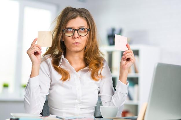 La bella donna d'affari di mezza età con gli occhiali lavora in ufficio