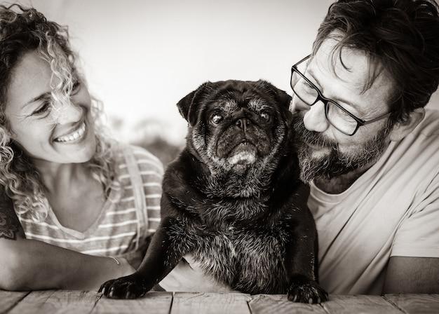 Bella coppia caucasica di mezza età che abbraccia il loro cane carlino con amore sorridente