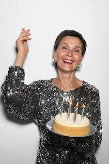 Bella donna di mezza età con in mano una torta di compleanno