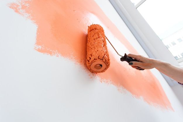 Bella donna di mezza età che dipinge la parete nel suo nuovo appartamento. concetto di ristrutturazione e ristrutturazione