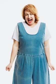 Una bella donna di mezza età con i capelli rossi urla emotivamente. vestito in tuta di jeans. muro bianco. verticale.