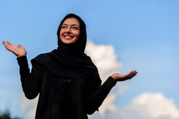 La bella donna mediorientale aspetta la pioggia.