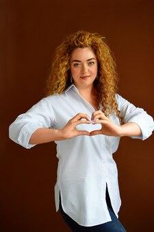 Bella ragazza di mezza età vestita con una camicia bianca sorride con amore facendo la forma di un cuore
