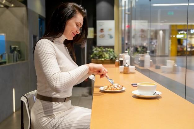 Bella donna di mezza età che mangia un croissant nella pausa pranzo di un bar