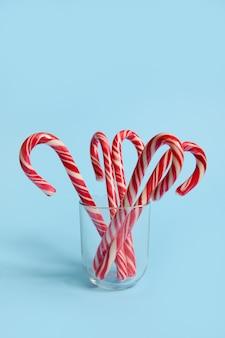 Bella composizione semplice e minimalista con bastoncini di zucchero su un vetro trasparente su sfondo blu con spazio copia per la pubblicità natalizia