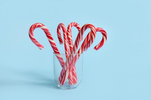 Bella composizione semplice minimalista con lecca-lecca di natale su vetro trasparente su sfondo blu con spazio copia per annuncio natalizio