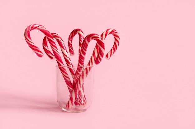 Bella composizione semplice e minimalista con lecca-lecca di natale su vetro trasparente su sfondo rosa con spazio copia per annuncio natalizio