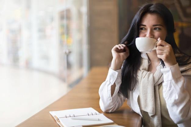 Bella razza mista femmina sorridente sognando diario di scrittura seduto alla caffetteria con tazza di caffè