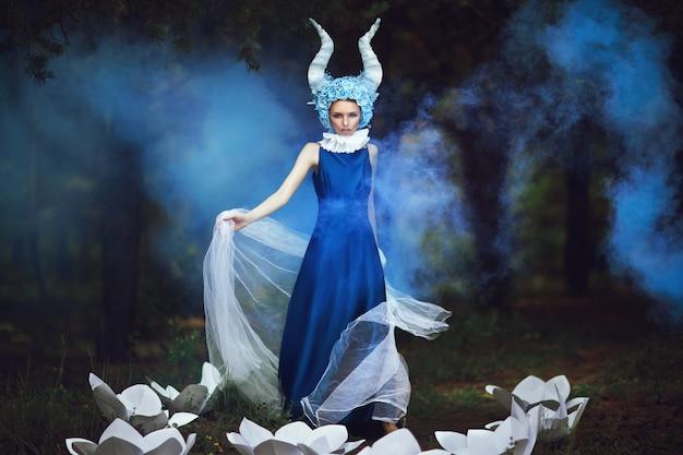 Il bello modello sta posando in una foresta con le corna blu