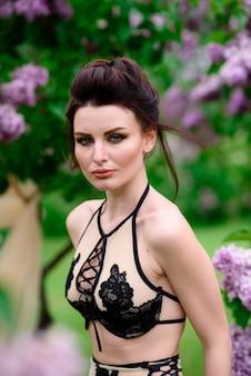 Bellissima modella in lingerie all'aperto con fiori sfocati sullo sfondo