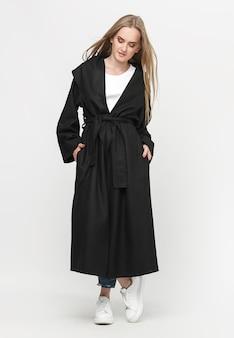 Bellissima modella in posa in un lungo cappotto nero su sfondo bianco