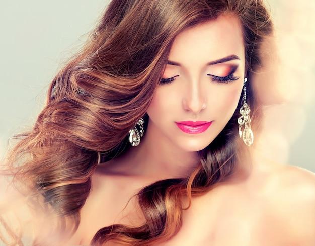 Bellissima modella con capelli lunghi, folti e ricci e trucco vivido con rossetto rosso. arte dell'acconciatura, cura dei capelli e prodotti di bellezza.