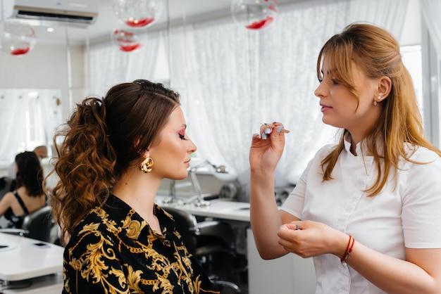 In un bellissimo e moderno salone di bellezza, una truccatrice professionista fa il trucco per una ragazza. bellezza e moda.