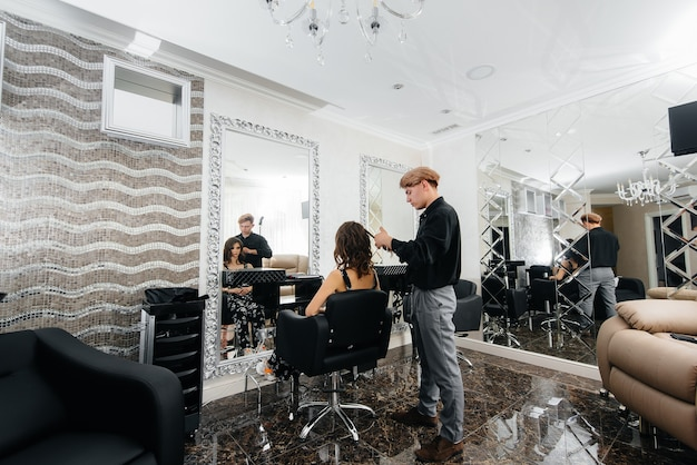In un bellissimo e moderno salone di bellezza, uno stilista professionista fa un taglio di capelli e un'acconciatura per una ragazza. bellezza e moda.