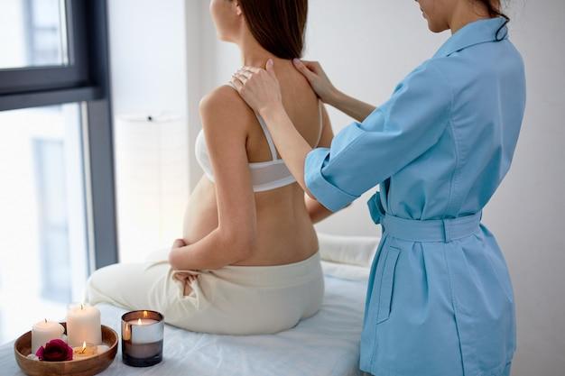 Bella futura mamma asiatica che si gode il massaggio alla schiena e alle spalle nella stanza dell'estetista nel centro benessere, vista laterale sulla signora rilassata seduta sul letto, fisioterapista femminile che fa massaggio. retrovisore