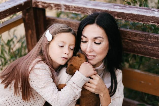 Bella mamma e figlia abbracciano il loro cagnolino marrone