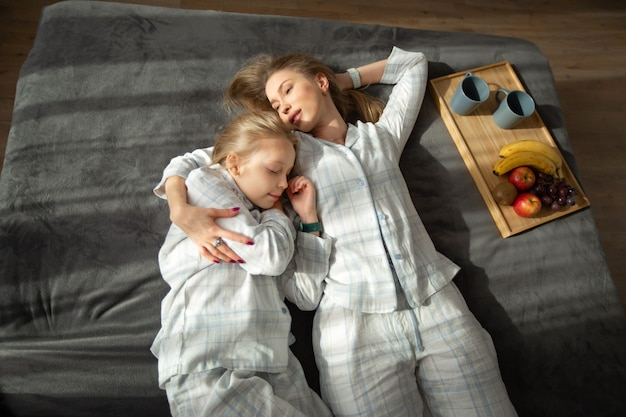 Bella mamma e figlia seduti a letto
