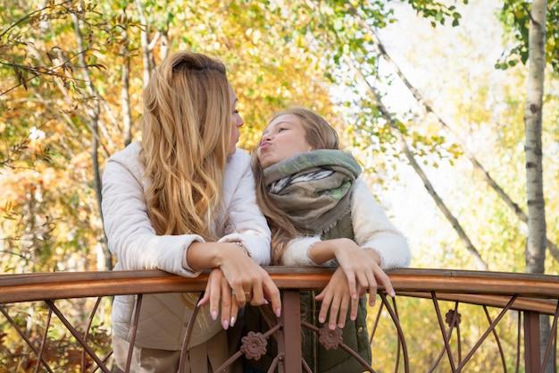 Bella mamma abbraccio figlia in pelliccia cuffie su sfondo colorato alberi di autunno sul ponte. weekend in famiglia, amore, relax all'aria aperta, divertimento, persone, stagione, clima caldo, foresta pittoresca