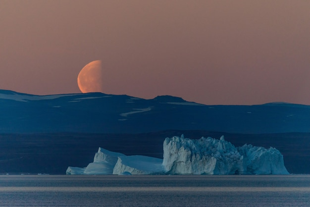 Bellissimo sorgere della luna in groenlandia. iceberg in mare.
