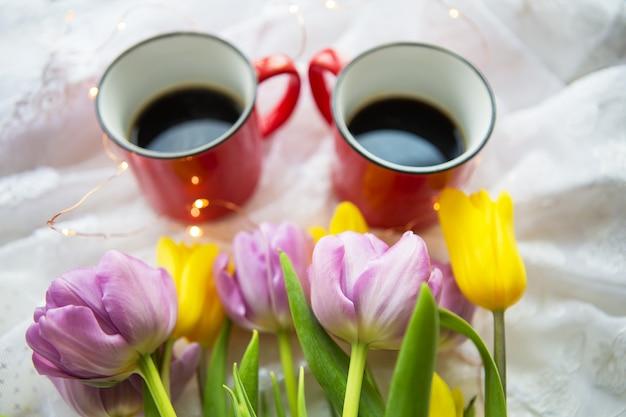 Bella mattina, due tazze di caffè e un mazzo di tulipani luminosi.