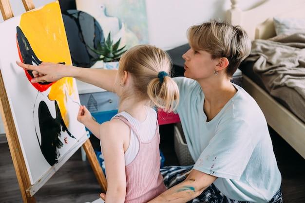 La bella madre artista e il suo bambino dipingono un quadro a casa con colori acrilici