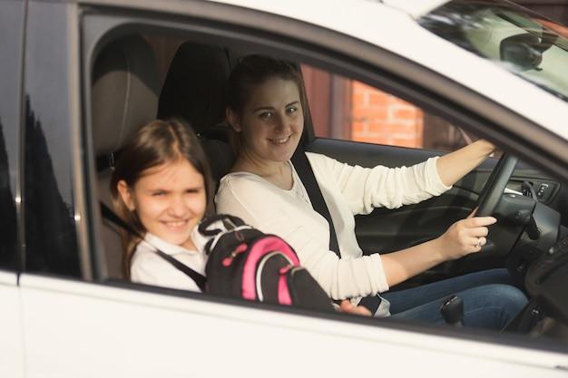 Bella madre che guida l'auto con la figlia a scuola