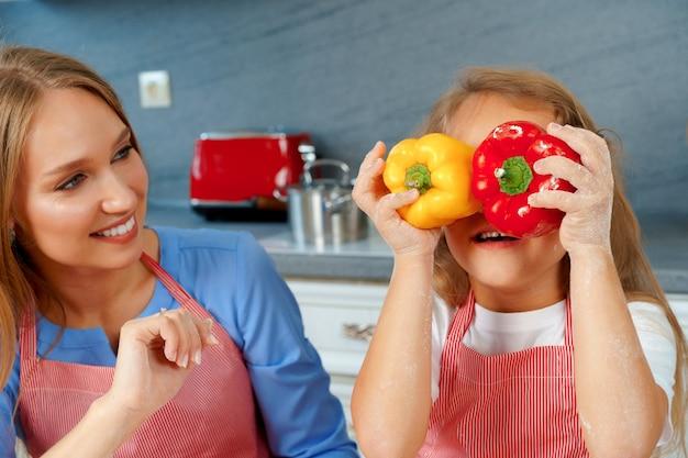 Bella madre e la sua adorabile figlia divertirsi in cucina mentre si cucina il cibo