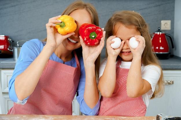 Bella madre e la sua adorabile figlia divertendosi in cucina