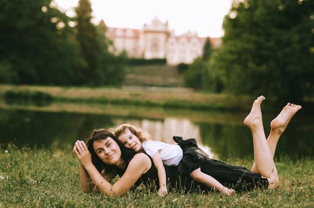 Una bella madre posa su un prato verde e giocando con sua figlia carina nel soleggiato parco estivo con un castello su uno sfondo