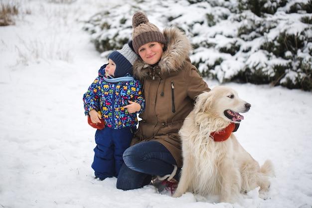 Bella madre e figlio che giocano con il mio cane nella neve. golden retriever