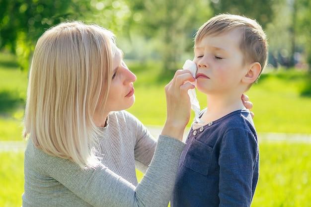 La bella madre pulisce il viso con i tovaglioli del bambino carino (figlio) nel parco su uno sfondo di erba verde e alberi