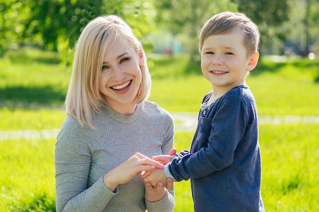 La bella madre si pulisce le mani con i tovaglioli del bambino carino (figlio) nel parco su uno sfondo di erba verde e alberi