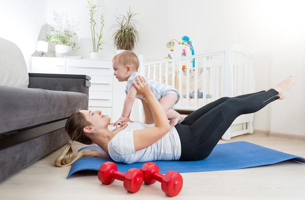 Bella madre con il suo bambino che fa esercizi fisici sul tappetino fitness in soggiorno